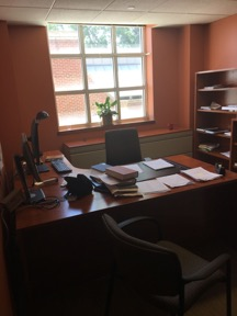 Office with desk, chair, computer, telephone, bookshelves and paperwork.